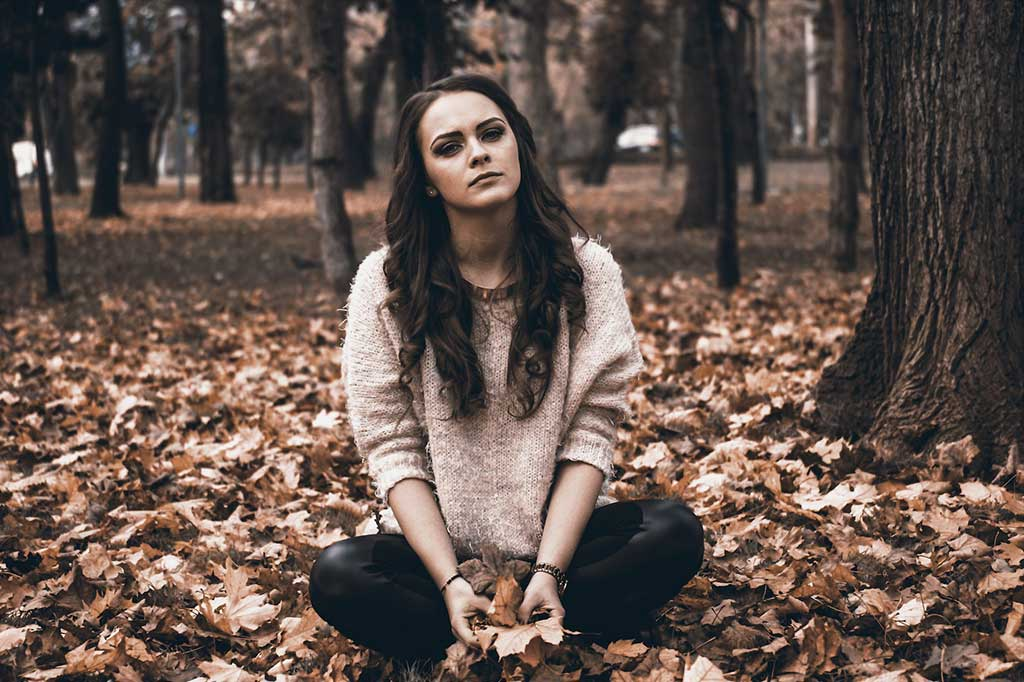Depressed teen girl sitting in the woods holding leaves