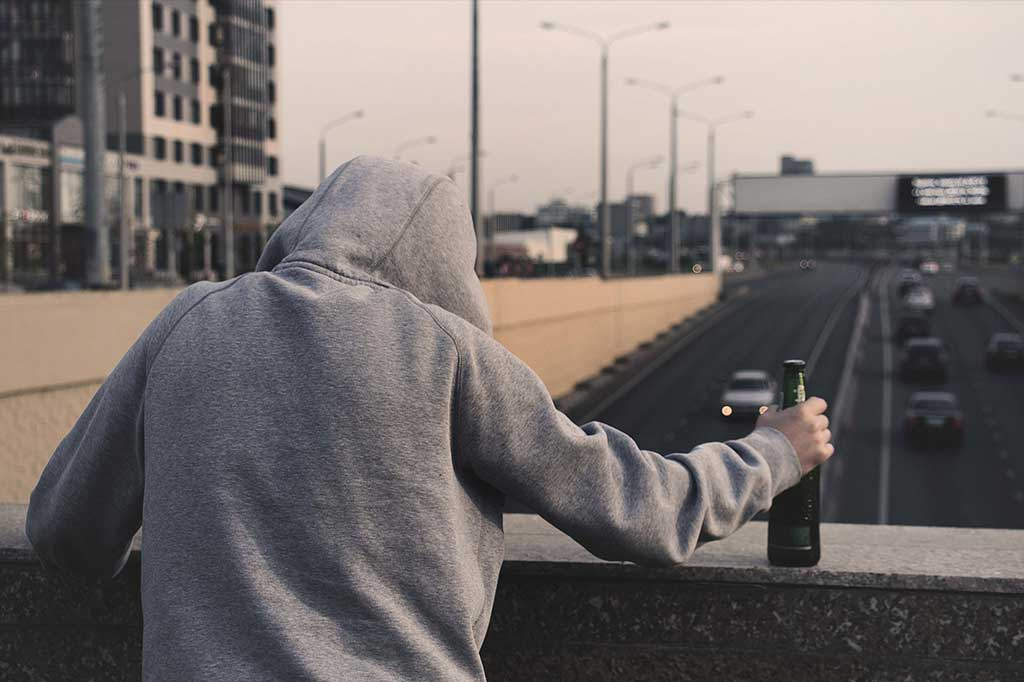 Male teen with beer on a bridge