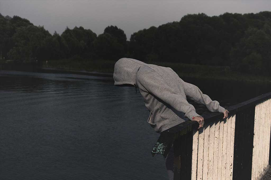 Male teen on bridge thinking about suicide